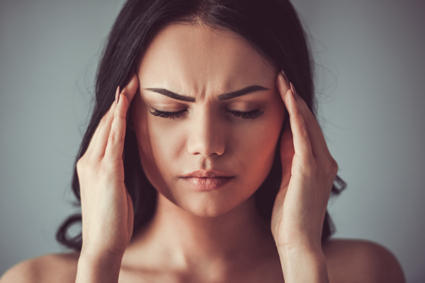 A woman holding her head for headache