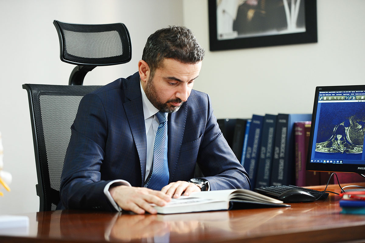 Dr. Aghayev at his desk reading a book